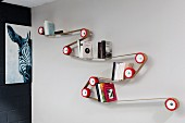 Designer bookcase made by winding strap around red rollers mounted on wall