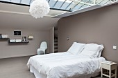 Minimalist attic bedroom with glass ceiling and taupe walls