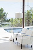 Two elegant white armchairs, arc lamp and side table in front of glass wall with view of pool