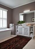 Elegant bathroom with taupe walls, rug, washstand and floor-mounted bathtub taps