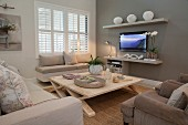 Scandinavian wooden table and window seat in seating area with flatscreen TV