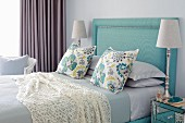 Elegant bedroom in shades of blue with turquoise upholstered headboard