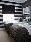 Kleiner Schlafraum mit zwei Einzelbetten, schwarz-weisse Blockstreifen auf Fensterwand mit schwarzem Stoffrollo