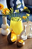 Vase of gerbera daisies and freesias, china dogs and tealight holders on coffee table