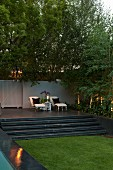 Vintage-style loungers and candle on side table on raised terrace with steps next to lawn