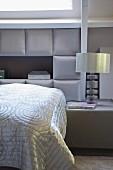 Schlafzimmer in eleganten Grautönen, auf Bett glänzende Tagesdecke vor gepolsterter Kassettenverkleidung an Wand, seitlich Nachttisch mit Tischleuchte