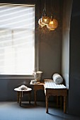Carved bench and side table below pendant lamps next to window with closed blinds in corner of grey-painted room