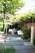 Terrace with wooden floor, outdoor shower and woman sitting in comfortable seating area below pergola