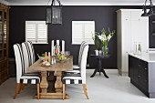 Open-plan kitchen with dining set in front of black-painted wall and closed interior shutters on windows