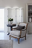 Antique armchair next to bistro table in front of white shutters on terrace doors