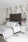 Bedside cabinets flanking double bed with tall headboard against wall covered in floral wallpaper