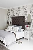 Nachtschränkchen neben Doppelbett mit hohem Kopfteil an tapezierter Wand mit floralem Muster