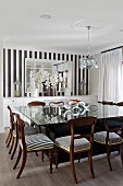 Large square glass table and various upholstered wooden chairs in dining room