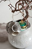 Spherical bauble made from old book pages hanging from tree