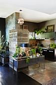 Unterschiedliche Materialien im Wohnraum mit offener Küche, von Rustikal bis Edel, belebt mit Grünpflanzen