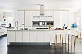 White, designer kitchen with bar stools at counter in open-plan interior