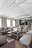 Upholstered furniture around coffee table below exposed roof structure in open-plan interior