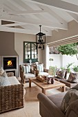 Comfortable seating area with wicker sofa set on tiled floor, fireplace and open French windows