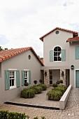 Wohnhaus mit sandfarbener Fassade und pastellgrünen Fensterläden, Pflanzkübel auf Pflasterboden vor Eingang