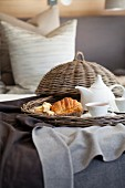 Croissant and tea on wicker tray on bed