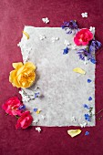 Frame of roses, cornflowers and hydrangea flowers around sheet of paper
