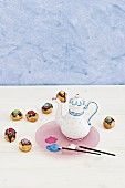Paintbrushes, coffee pot painted with porcelain paint and cake pops with colourful decoration