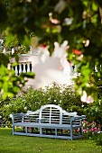 Gartenbank im Garten vor einem Staudenbeet mit Rosen und Petunien
