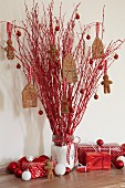 Jar of red twigs decorated with felt gingerbread houses and gingerbread men