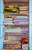 Folded bedclothes in a pastel blue laundry cupboard