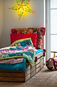 DIY bed made from wooden crates with colourful patchwork blankets below glowing, star-shaped lamp