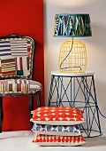 Stacked patterned cushions in front of table lamp on side table next to char with graphic patterns on upholstery