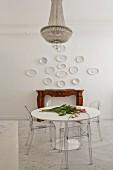 Tulpen liegen auf rundem Tisch mit Ghost Chairs vor Kaminkonsole und Wandtellern