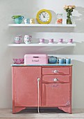 Battered pink kitchen cabinet below crockery on white floating shelves