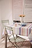Teeservice auf Tisch mit gestreifter Tischdecke, hellgraue Klappstühle vor Fenster mit Innenläden