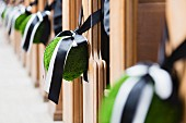 Baubles tied to church pews with ribbons as wedding decorations