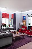 Sessel mit rotem Samtbezug und Holztisch in Wohnzimmer mit traditionellem Flair, im Hintergrund Sitzberecih im Erker