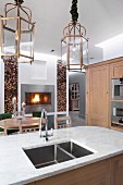 Kitchen island with pale marble top and integrated sink below lantern-style pendant lamps; dining area with fire in fireplace in background