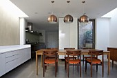 Pendant lamps with metal lampshades above dining set in open-plan kitchen