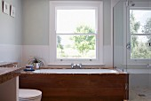 Fitted bathtub with wooden sides below window next to glass shower screen