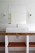 Washstand with countertop sink on marble counter against wall with half-height white tiles below mirror flanked by sconce lamps
