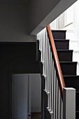 Treppenhaus mit schwarzem, läuferartigem Streifen auf weissen Holzstufen