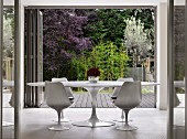 White, classic Tulip Table and matching chairs in front of open folding chairs with view into garden