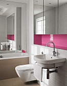Sink with towel rail below pink niche with fitted, mirrored cabinets in bathroom