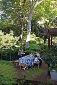 Familie mit Kind und Hund auf Holzterrasse, gedecktem Tisch, umgeben von tropischen Pflanzen
