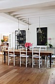 Langer Holztisch mit Vintage-Holzstühlen in offenem Wohnbereich