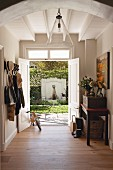 Coat rack and open double doors in hallway of renovated country house