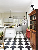 Chequered floor, rustic cabinets and old bookcase in open-plan kitchen