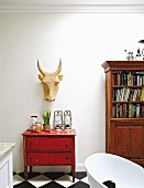 Carved ox head above old, red chest of drawers next to bookcase