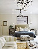 Striped sofa and footstool at foot of bed in elegant bedroom in mixture of patterns