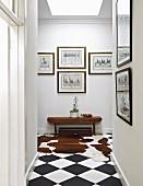 Bildergalerie im Flur mit Kuhfell auf dem Schachbrettboden